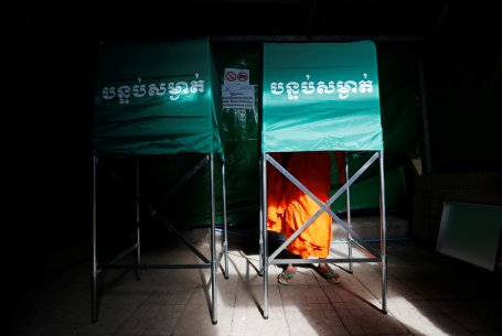 A Buddhist monk votes at a polling station during a general election in Phnom Penh