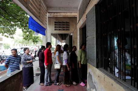 People line up to vote at a polling station during a general election in Phnom Penh